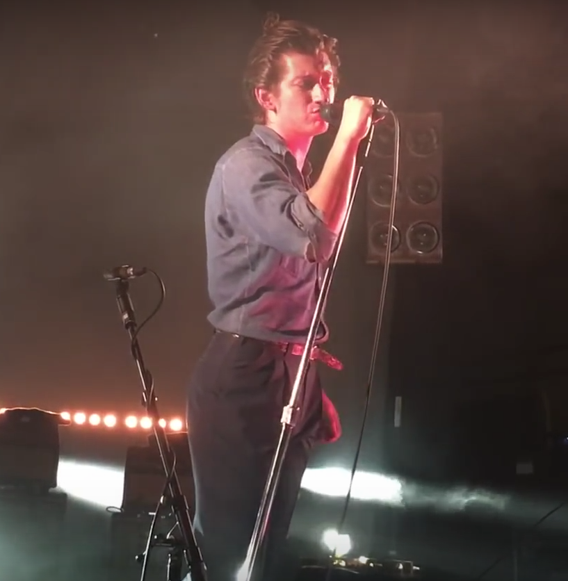 "Turner sing's "" The Dream Report "" live in the UK: his slicked back hair and shirt tucked into high waisted pants reflects the music he is performing."