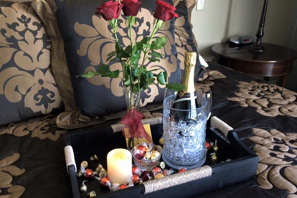 bubbles, roses and chocolates in guest room for romantic getaway