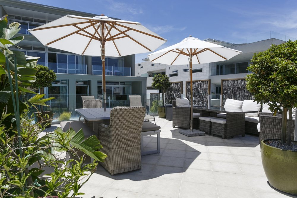 Patio area by pool with outdoor furniture looking towards main block-min.jpg