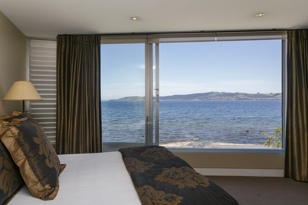 First floor three bedroom apartment master bedroom showing large widow with lake and mountain views 2.jpg