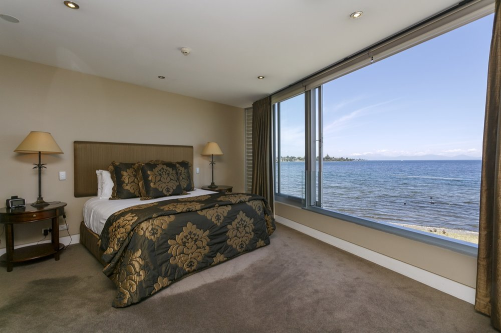 First floor three bedroom apartment master bedroom showing large widow with lake and mountain views.jpg