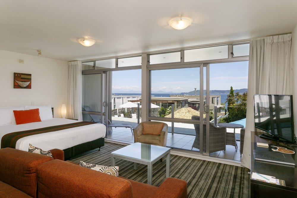 Luxury Studio with Lake Views living area and bed looking towards balcony showing lake views-min.jpg