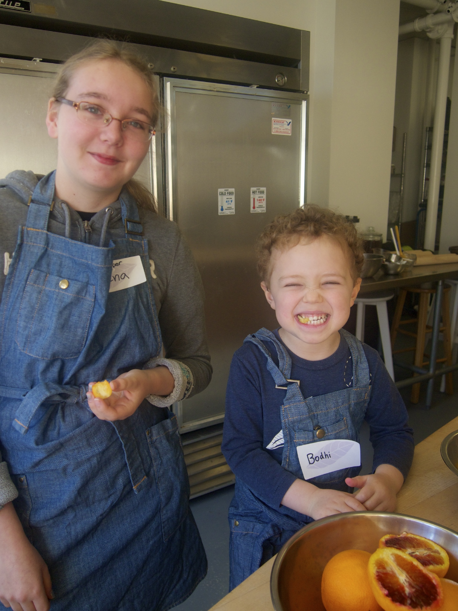 Enjoying kumquats: Jr. Chef Helper Elena with Bodhi