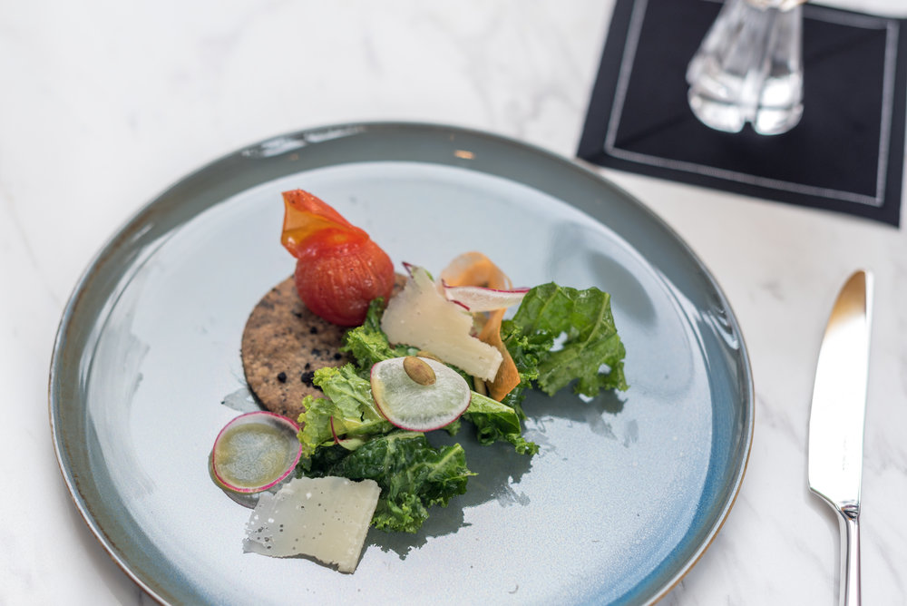 Local Kale Salad with Black Olive Cookie, Baby Heirloom Tomatoes, Toasted Pumpkin Seeds and Passion Fruit Vinaigrette  Racines - Sofitel Singapore City Centre