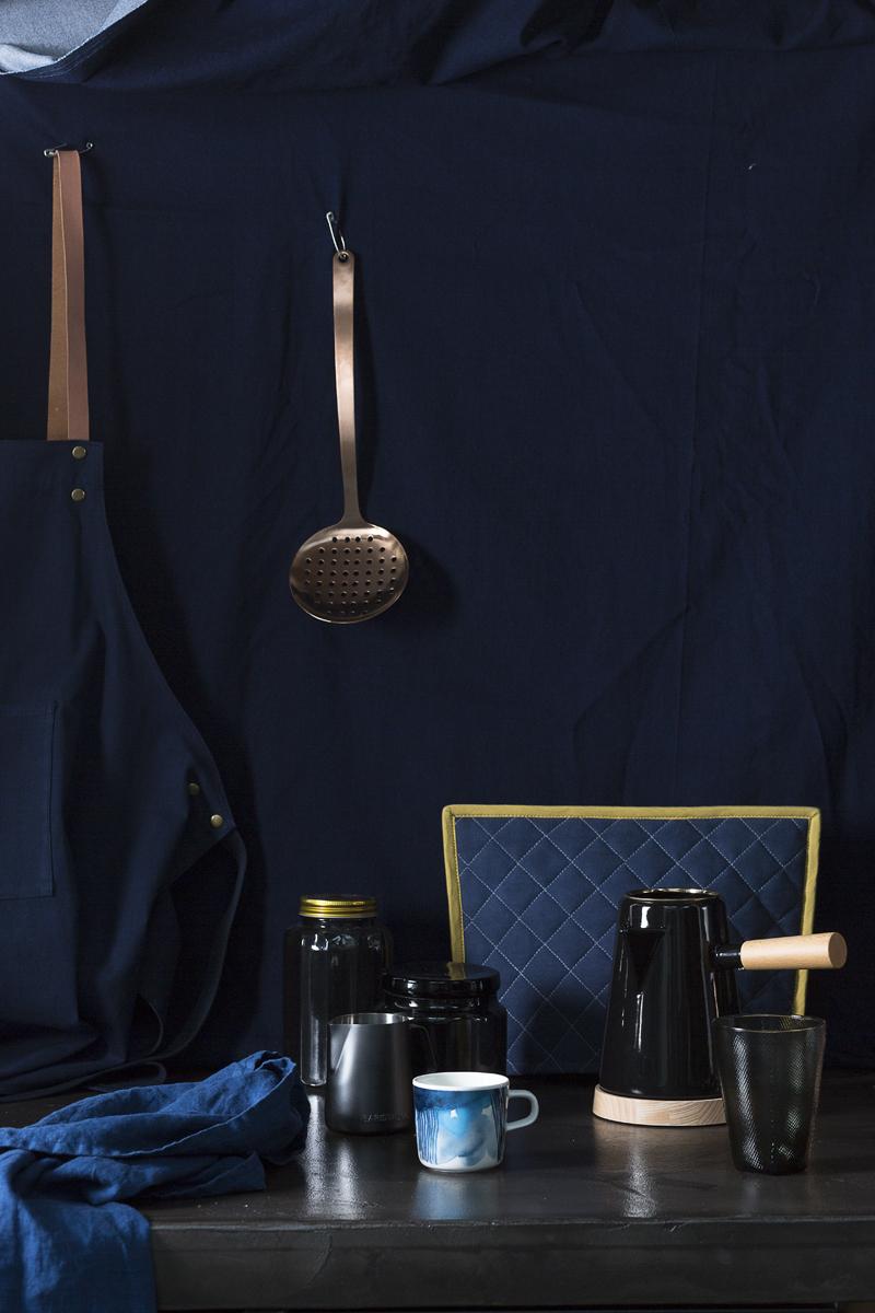 Tafelloper van H&M Home, Glazen voorraadbus met gouden deksel van H&M Home, Melkkannetje van &Klevering, Glazen voorraadpot van H&M Home, Beker met blauwe verf motief 'Marrimekko' via &Klevering, Koffiepot van Restored, Glas van &Klevering, Theemuts van Ferm Living, Schort van Ferm Living, Opscheplepel van Hema