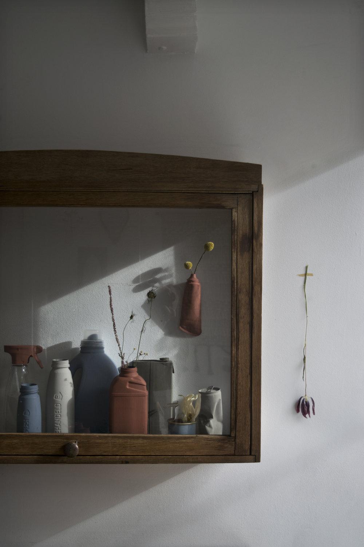 Wandkast ( kieveen.nl ), spuitfles (afval Spuistraat, Amsterdam), licht blauwe en licht grijze fles (afval  albertheijn.nl ), wasmiddel fles, (afval Herengracht, Amsterdam) roze fles, (afval Dijksgracht, Amsterdam) melkpak, visblikje, drinkblik (afval  stylecookie.nl ), gedroogde tulp (afval  stylecookie.nl )