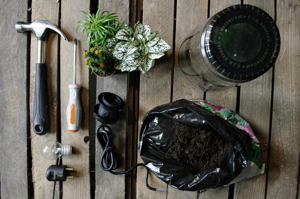 Benodigdheden: Grote (augurken) pot met metalen deksel, fitting, snoer, stekker, peertje, hamer, schroevendraaier, spijker, stift, plantjes naar keuze.