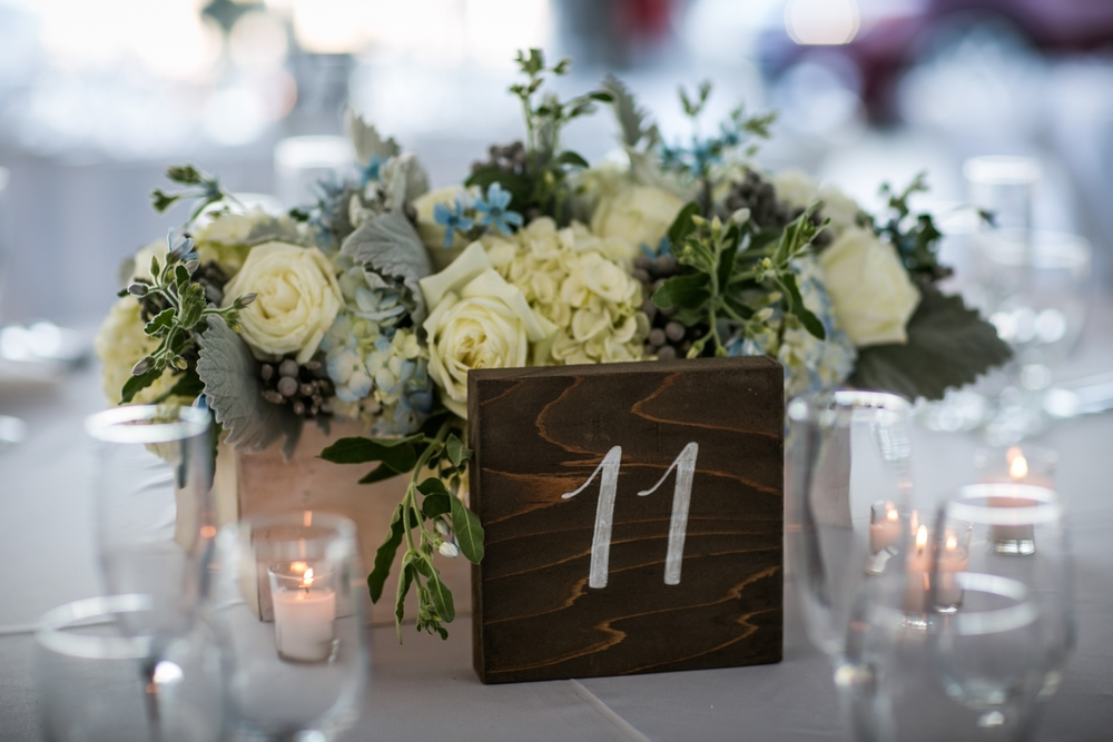 All white linens and chairs, set a clean and simple beachy look accented with rustic touches. Lily in the Valley created centerpieces of hydrangea and garden roses, of which echoed the shades blues in the couple's wedding invitations.