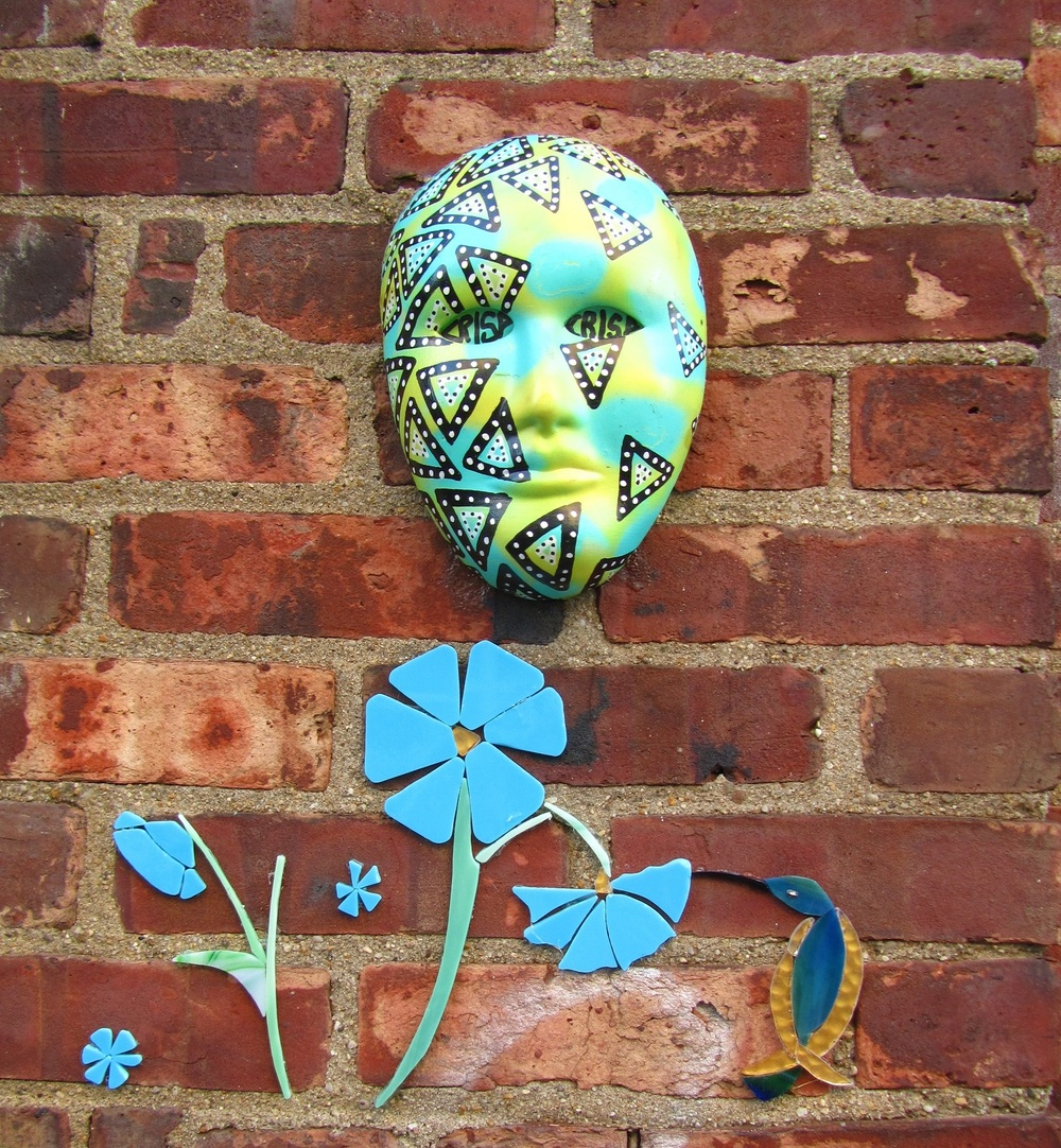Blue glass flowers with blue and gold hummingbird beneath crisp's 3D face mask