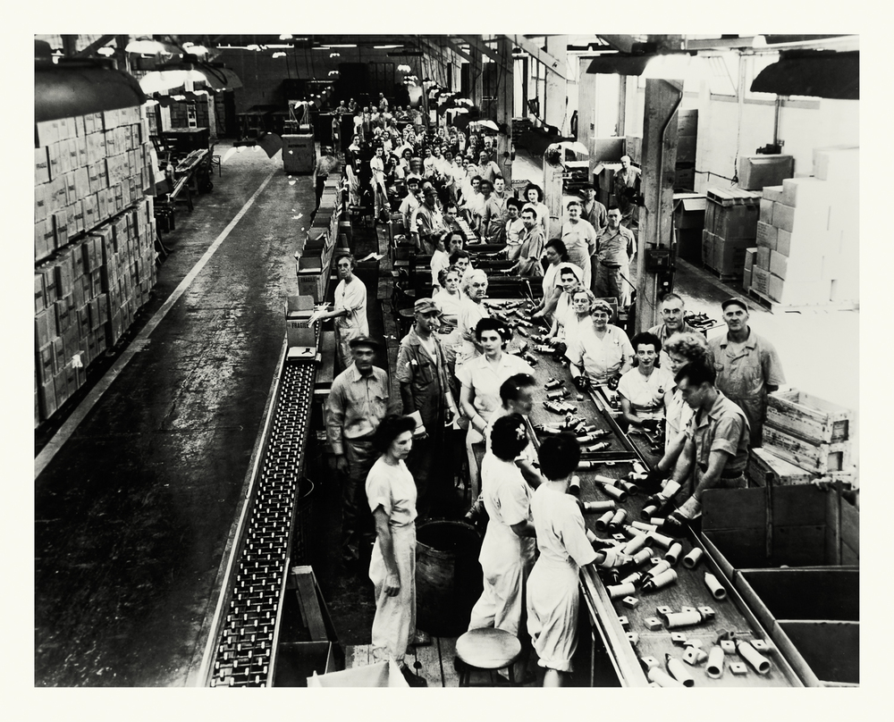"Photograph No. PD 142. ""Photograph depicting a line of workers assembling Variable Timing fuses for rockets. These fuses used reflected radio waves to detect proximity to a target which would then trigger the explosion. Factory located at the Hinghan Naval Ammunition Depot"" c., 1940 Records of Naval Districts and Shore Establishments, RG 181, NARA Boston."