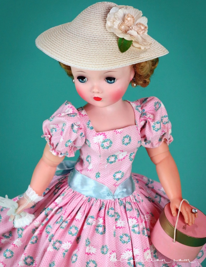 Cissy wears a 1957 polished cotton wreath print dress with puff leaves and a blue satin sash.