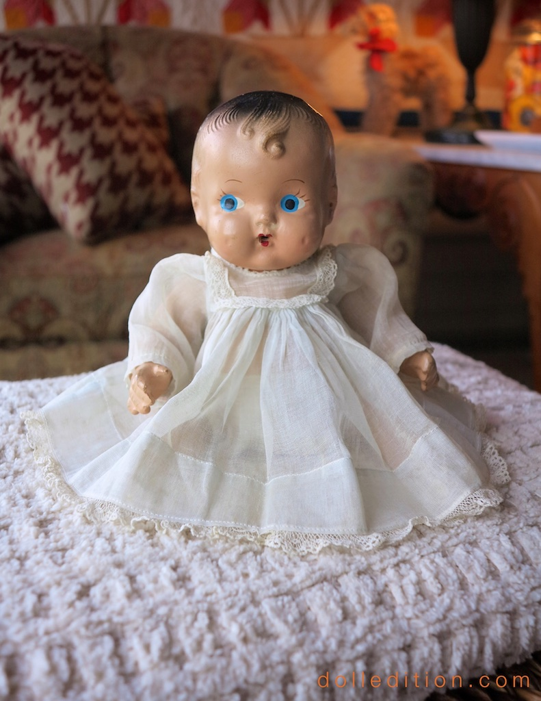 The doll has bent arms and adjustable legs. Her diapers and gown both use safety pens - before the use of buttons or snaps.