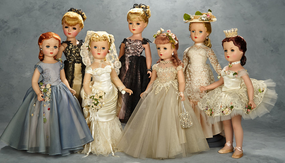 21 inch set of 1951 Mystery Portrait Dolls by Madame Alexander:Front, left to right: Judy, A Debutante; Victoria, a godey bride; Deborah, a Debutante; Ballets des Fleurs  Top, left to right: Champs-Elysées with golden sheath, Champs-Elysées with pink sheath; Pink Champagne, inspired by a Renoir painting
