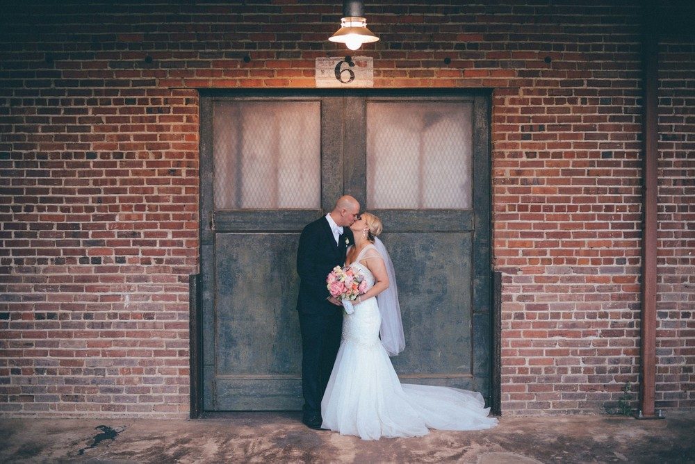 bride and groom kissing in front of door and brick wall at louisiana wedding