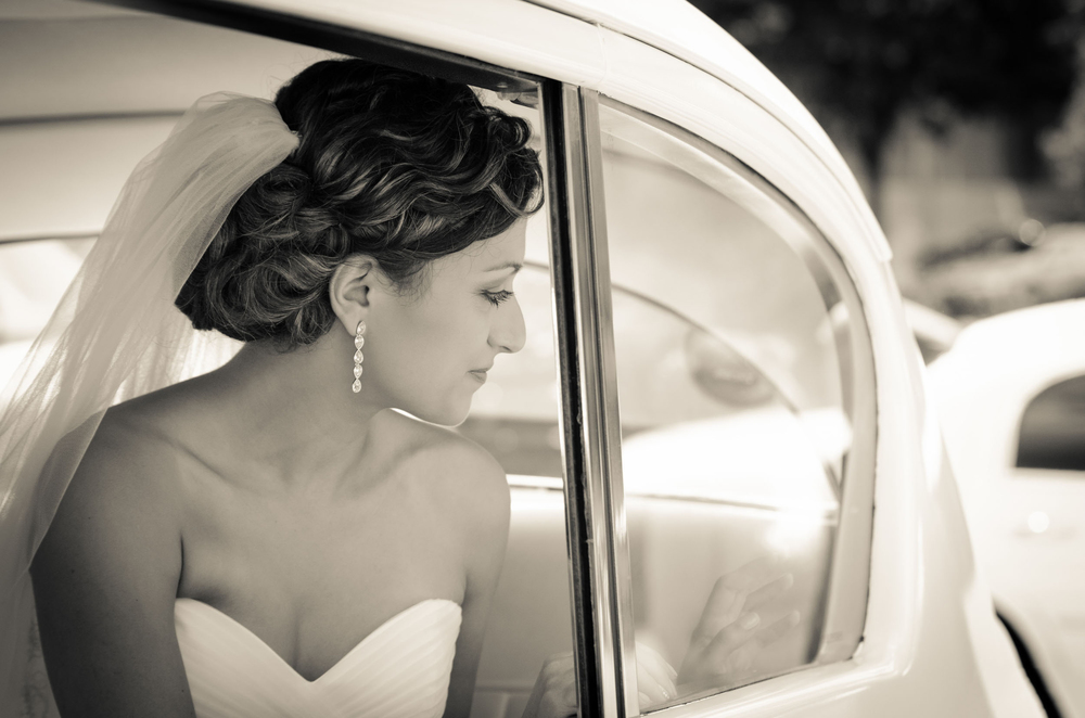 bride with veil looking out window of limousine