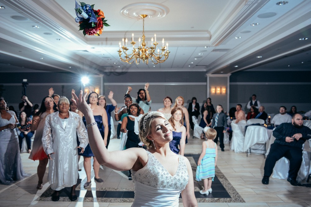 bride throwing bouquet over head at reception hall in monroe, la