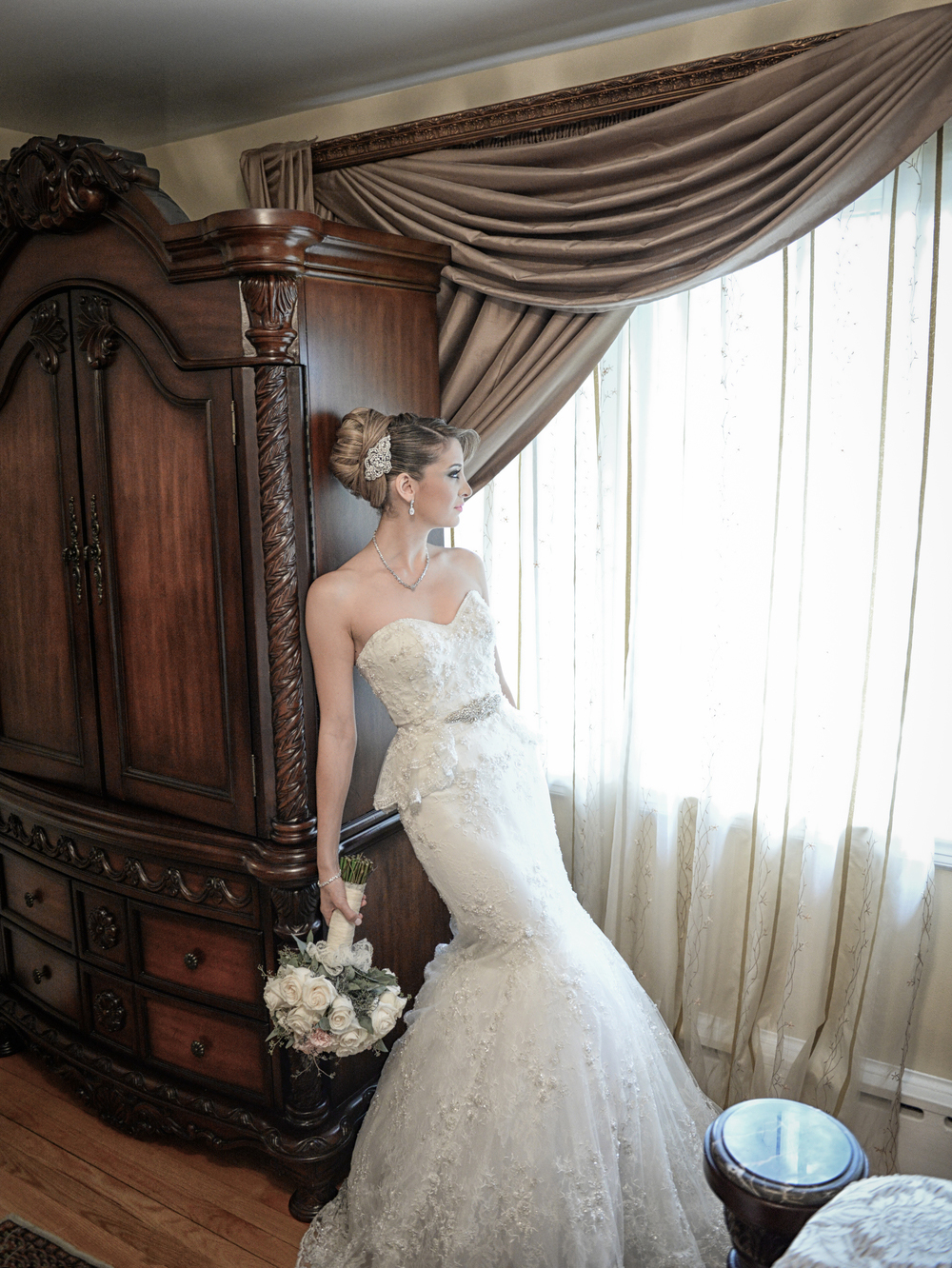 bride holding bouquet leaning against wooden furniture by window in monroe, la