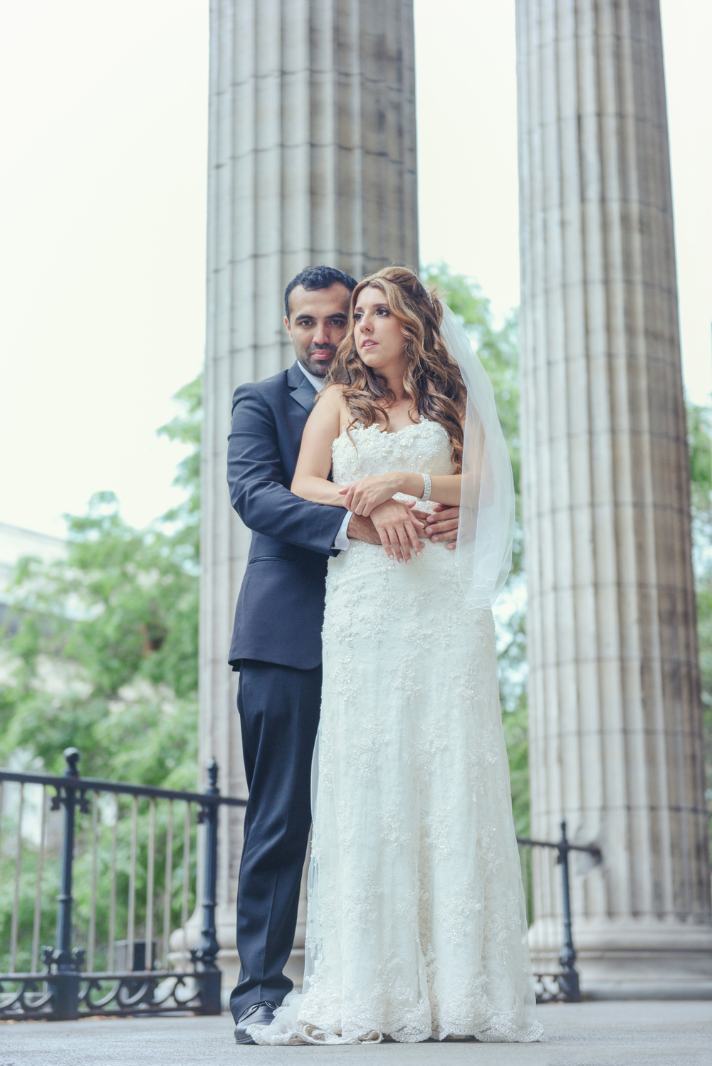 bride and groom standing by columns of building in monroe, la