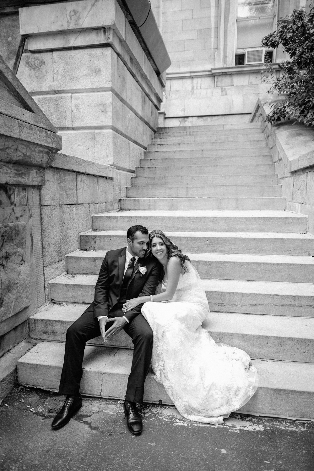 bride leaning on shoulder of groom sitting on steps of building