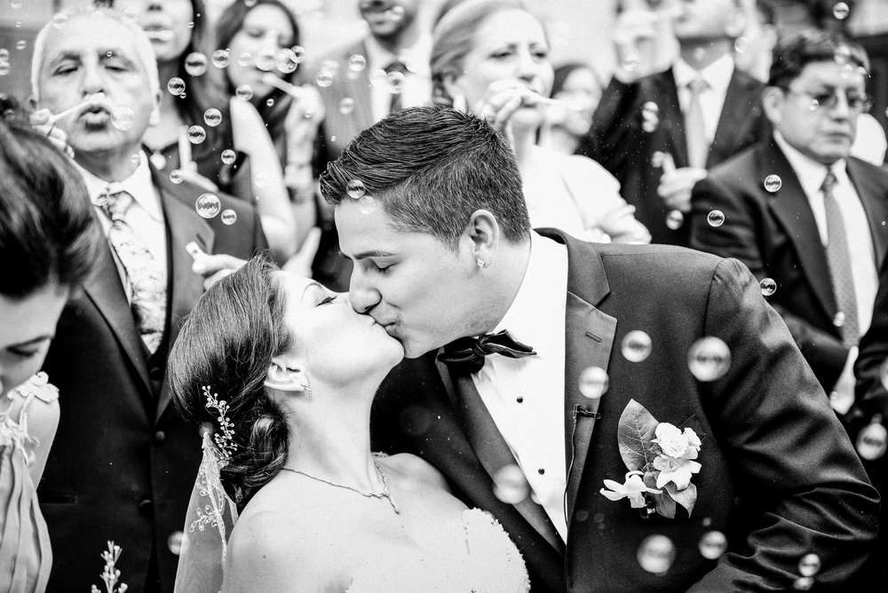 bride and groom kissing in front of crown with bubbles
