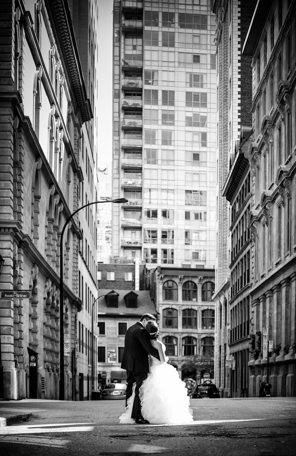 bride and groom kissing in front of tall buildings downtown monroe, la