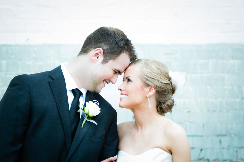 bride and groom touching foreheads in front of brick wall