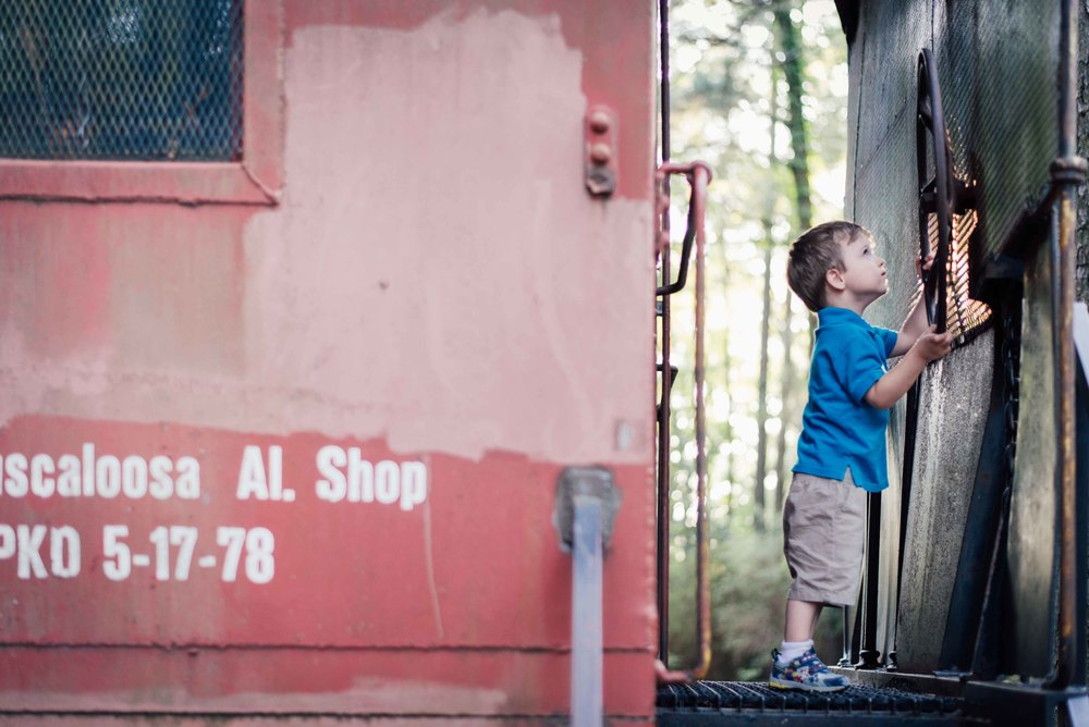 boy playing on caboose in kiroli park