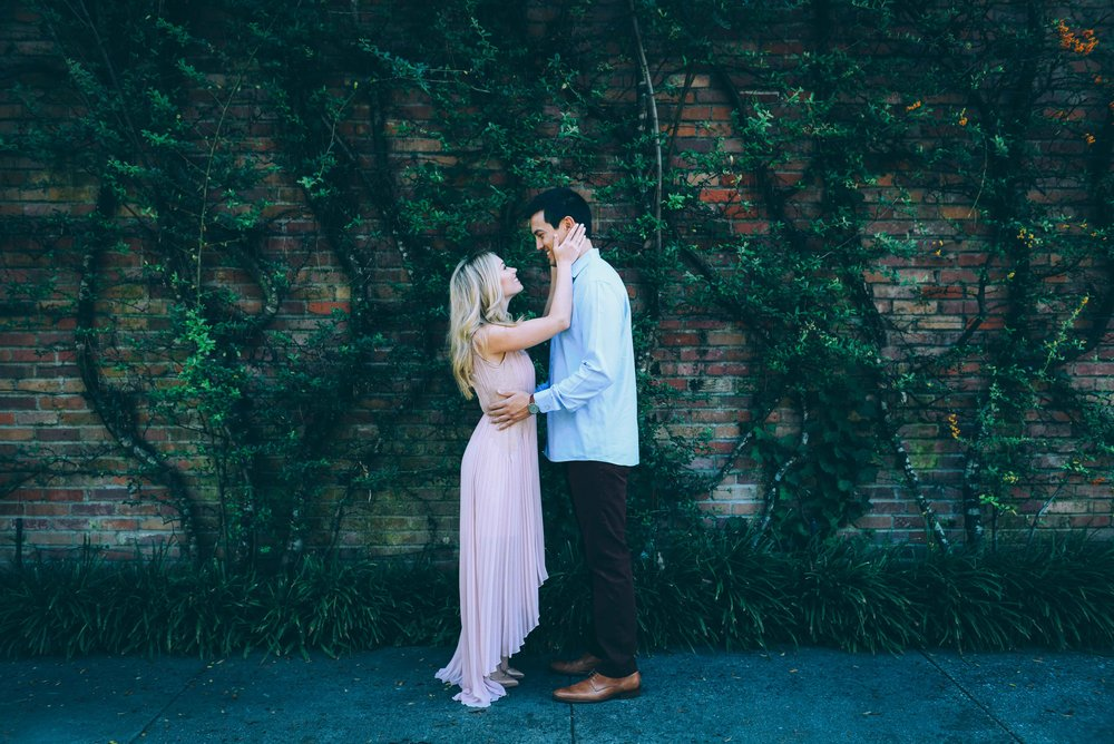 couple in front of vines on brick