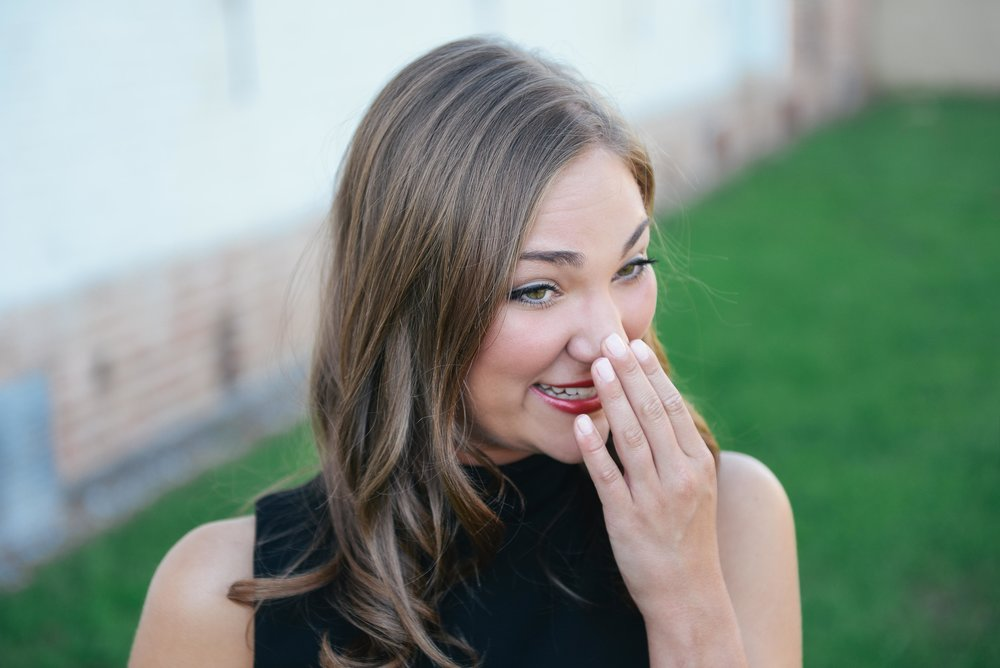 girl laughing with hand covering face