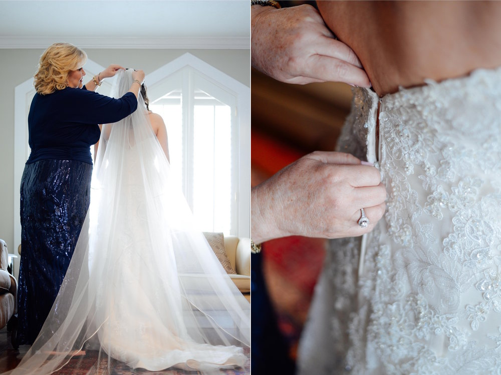 mom buttoning up daughter's wedding dress
