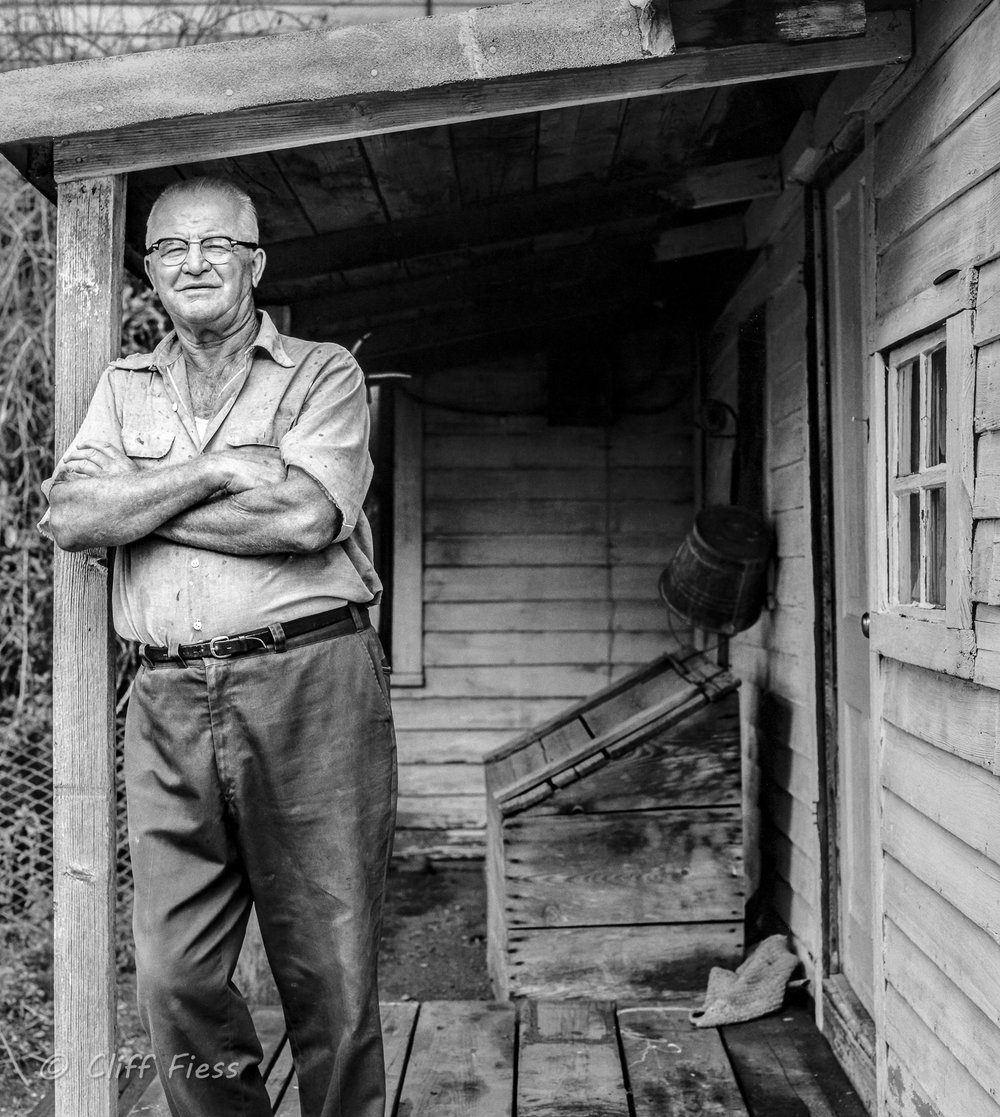 A portrait of a farmer on his front porch