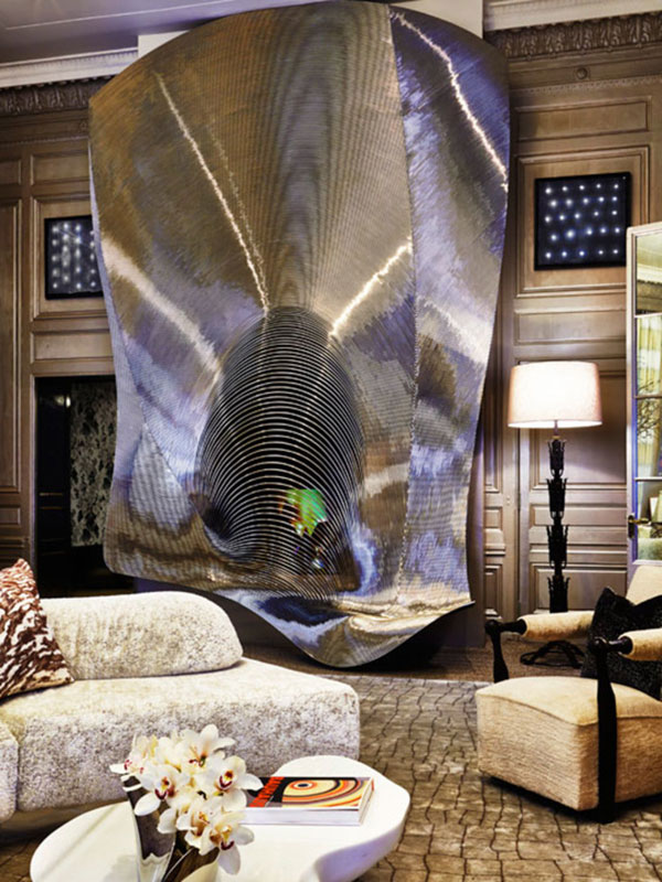 A floor-to-ceiling fireplace screen (above) that, to my eye, resembles a black hole. How are we supposed to throw another log on the fire if we are afraid of being sucked into an electromagnetic void?  Photo by Timothy Bell via Architectural Digest