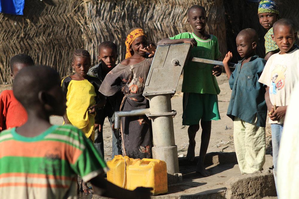 Children gather at the village well.