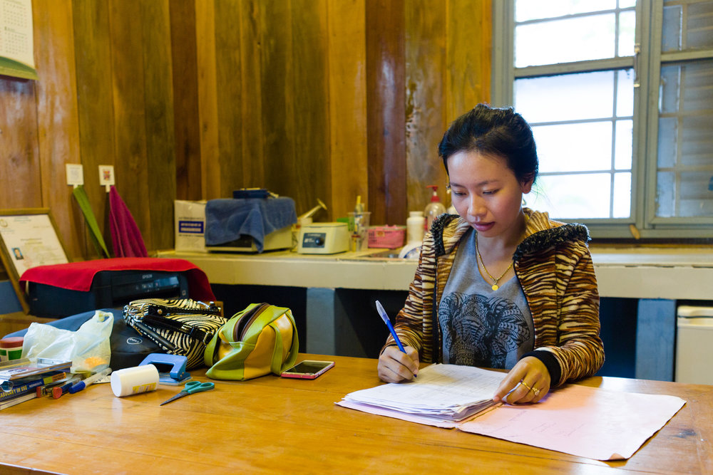 Sovanly, the nurse in charge of Mekong Blue's health clinic, checks through medical records.