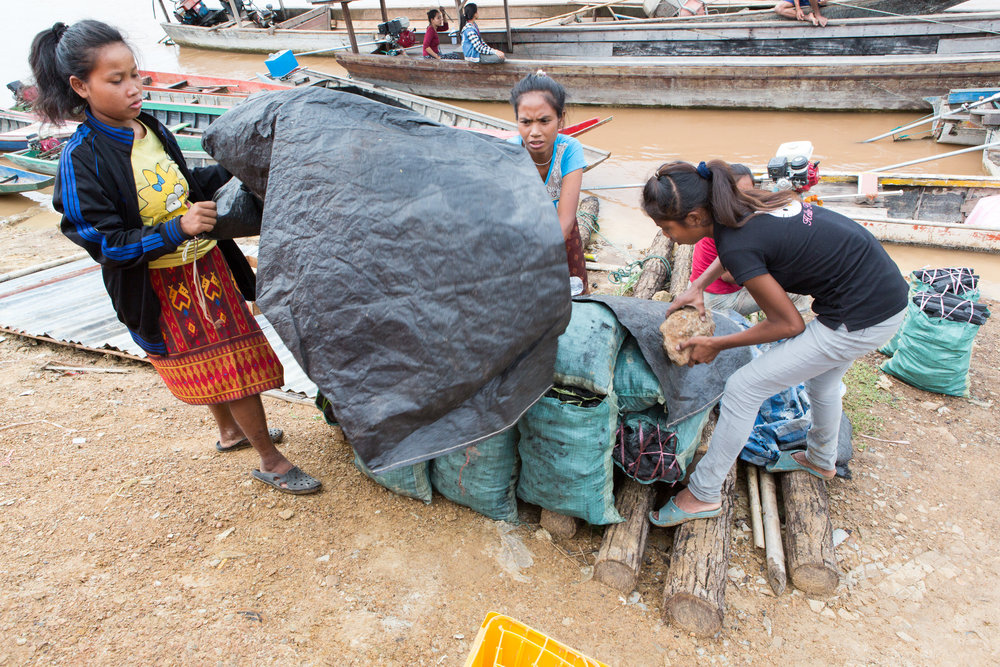In Nakasong, women cover a load of charcoal used to fuel cooking fires in the Mekong region.