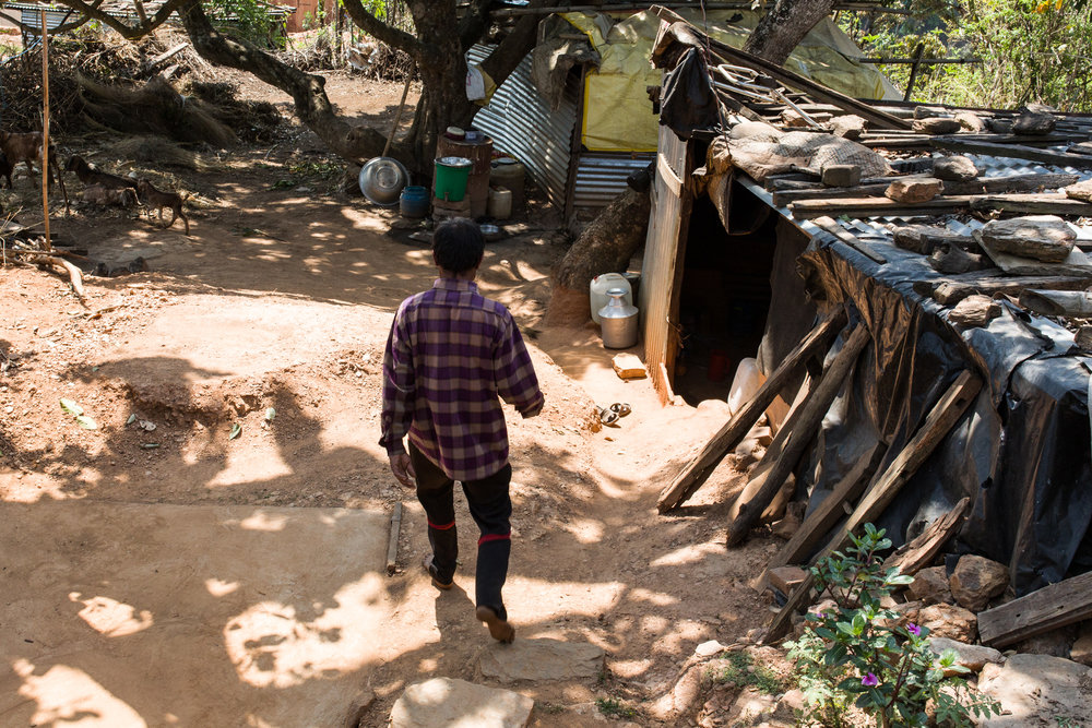 Narayan walks by the makeshift shack he and his family of seven slept in for a year.