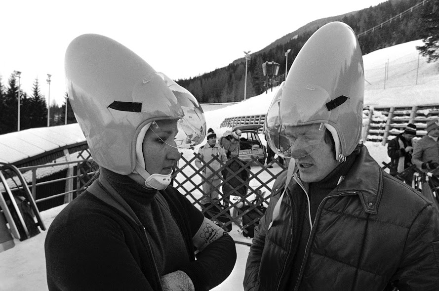 In 1976, members of the West German luge team, Elisabeth Demleitner and Stephan Hoelzlwimmer, wear the latest design in helmets during a practice session on the Olympic Luge course in Innsbruck, Austria, on Friday, on January 30, 1976.