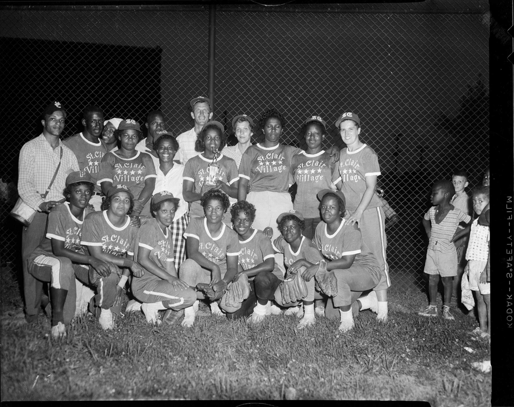 Women's St. Clair Village softball team with trophy, on playing field at night, c. 1950–1970,