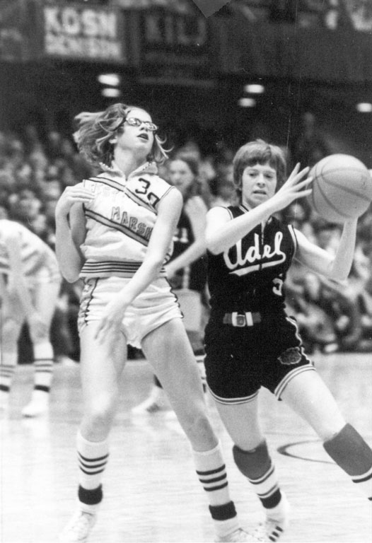 Julie Goodrich evades block on the basketball court, Adel, Iowa, early 1970s.
