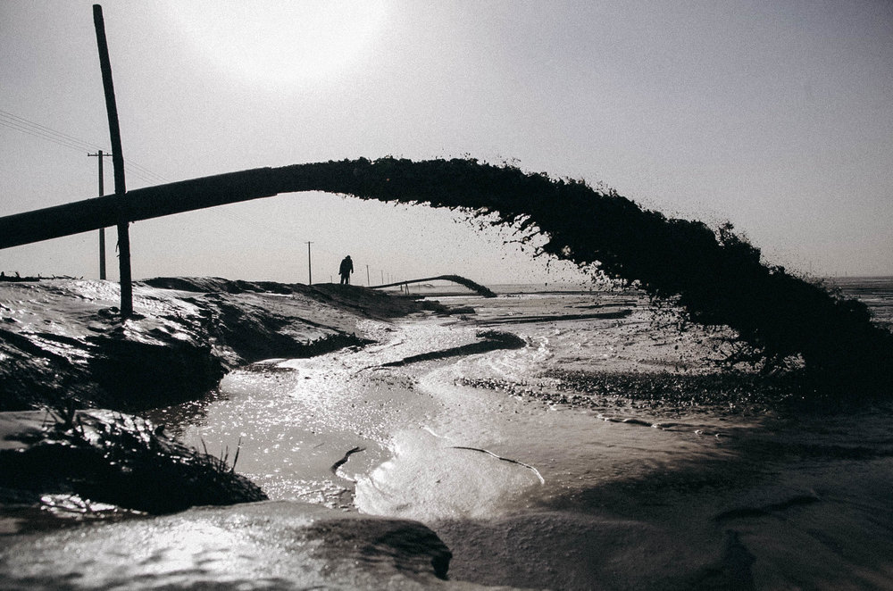 """Rare earth discharge liquid outflows from a pipeline into a """"rare earth lake"""" near Xinguang village on Nov. 26, 2010 in Baotou, Inner Mongolia of China."""