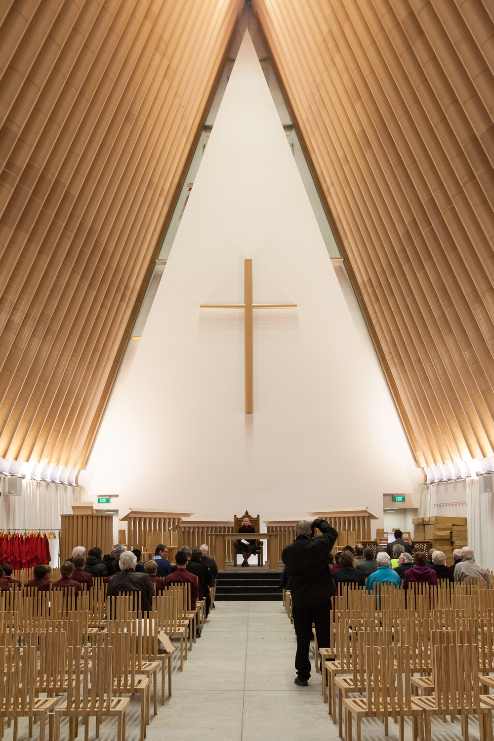 Monastic in its simplicity, the cardboard crucifix appears to float above the congregation