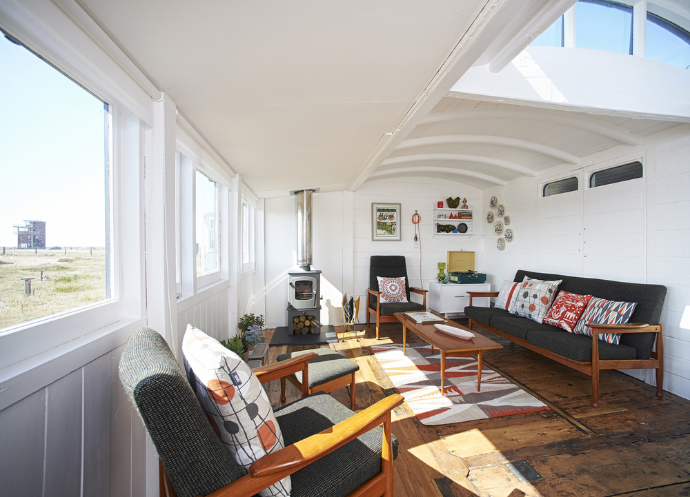 The living room mixes British mid-century furniture such as this Guy Rogers sofa and armchairs with Mini Moderns designs