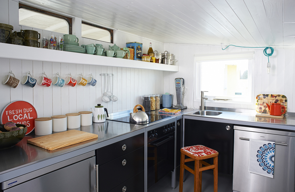 An IKEA 'Udden' kitchen is decorated with Mini Moderns kitchenalia and vintage finds. 'Because the entire house is wood clad,' says Keith, 'we went with stainless steel surfaces, which are reminiscent of a fishmonger's preparation area'