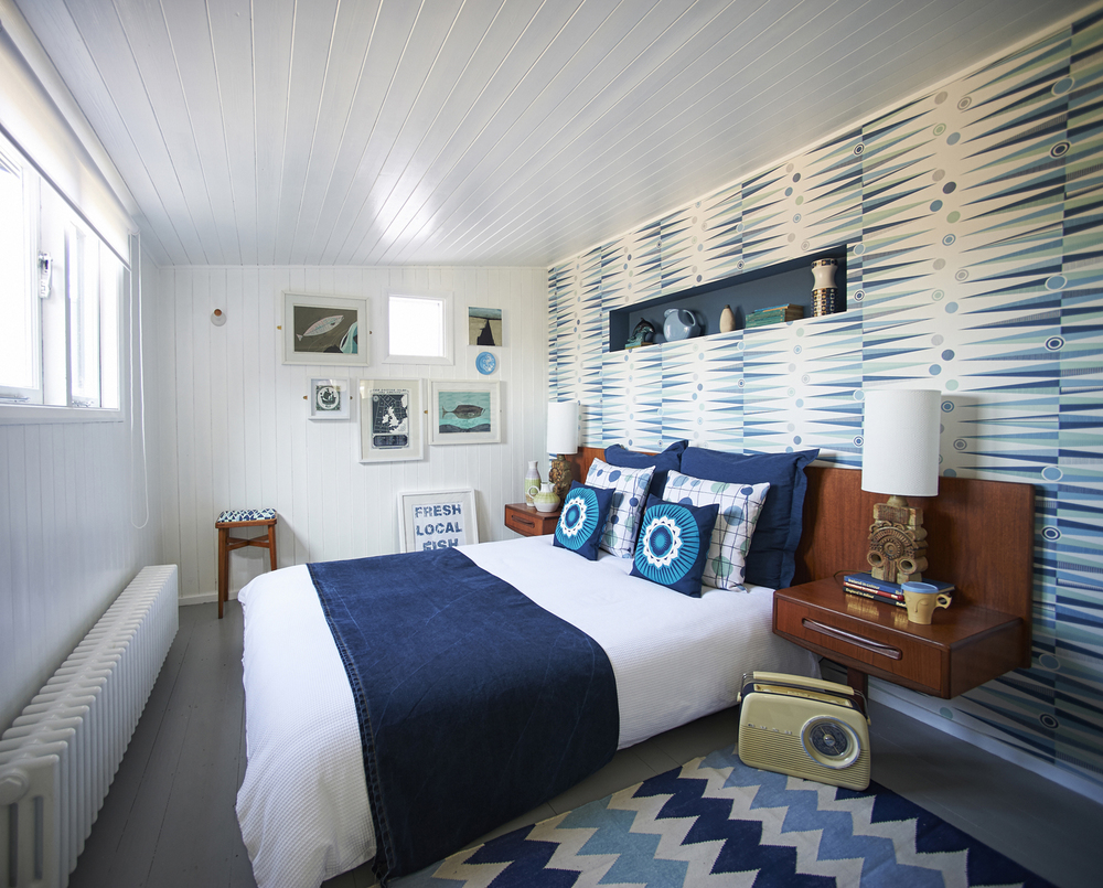 In a funky geometric and G Plan scheme, the bedroom sports Mini Modern designs including the 'Backgammon' wallpaper, 'Zag' dhurrie and 'Pavilion' cushions
