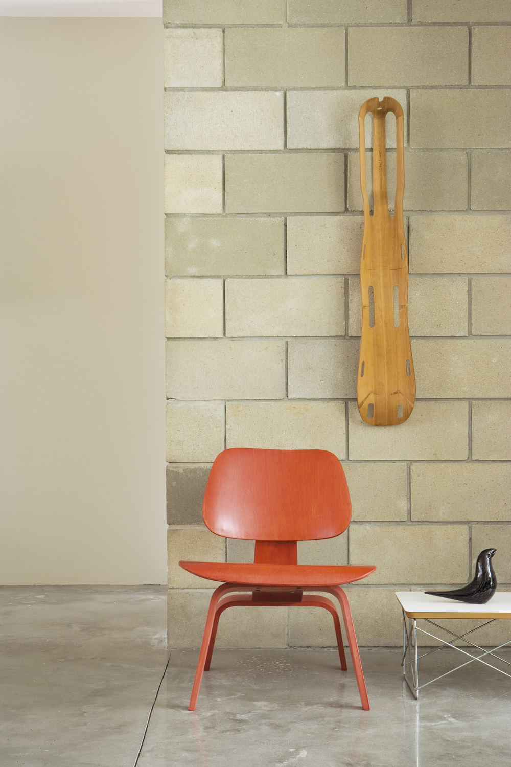 E is for Eames... A plywood splint designed by Charles and Ray Eames for the US Navy hangs above a red Eames 'DCW' chair