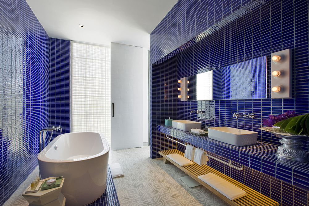 Blue tiles in bathrooms reference the Andaman Sea, offset by white and grey Sino-patterned floor tiles. A sculptural bath and double basins are sleekly contemporary; theatrical lights and an ornate urn add glamour