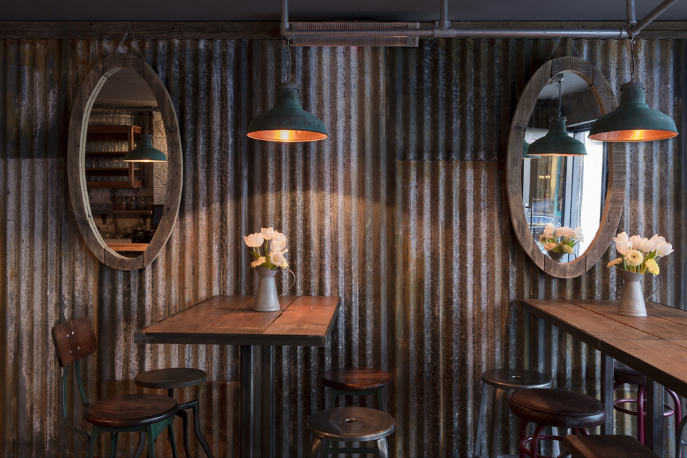 RUSTIC CHIC: the austere corrugated walls are offset with moody lighting, wood and simple floral arrangements