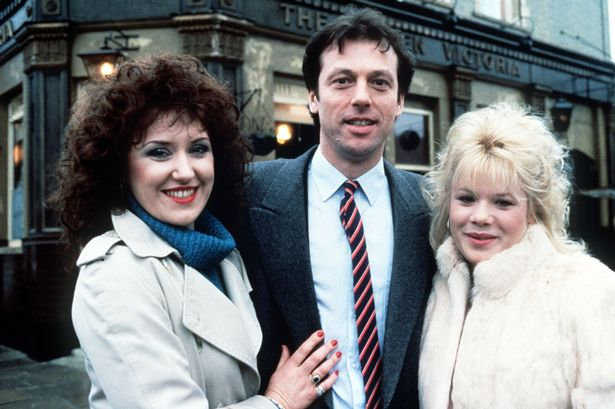 TV Progs Eastenders  Angie, Den and Sharon Watts standing outside the Queen %22Vic%22 Victoria pub in Albert Square Anita Dobson, Leslie Grantham and Letitia Dean.jpeg