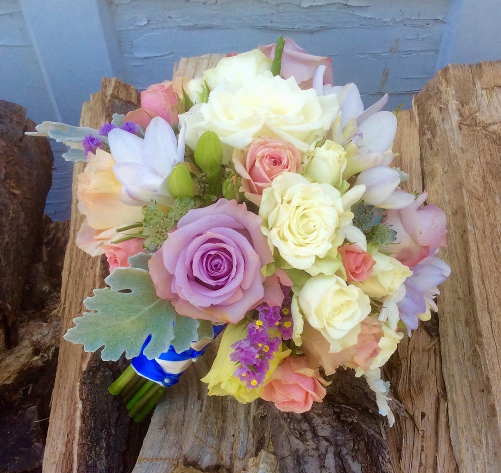 Roses, freesia, statice, spray roses and dusty miller.