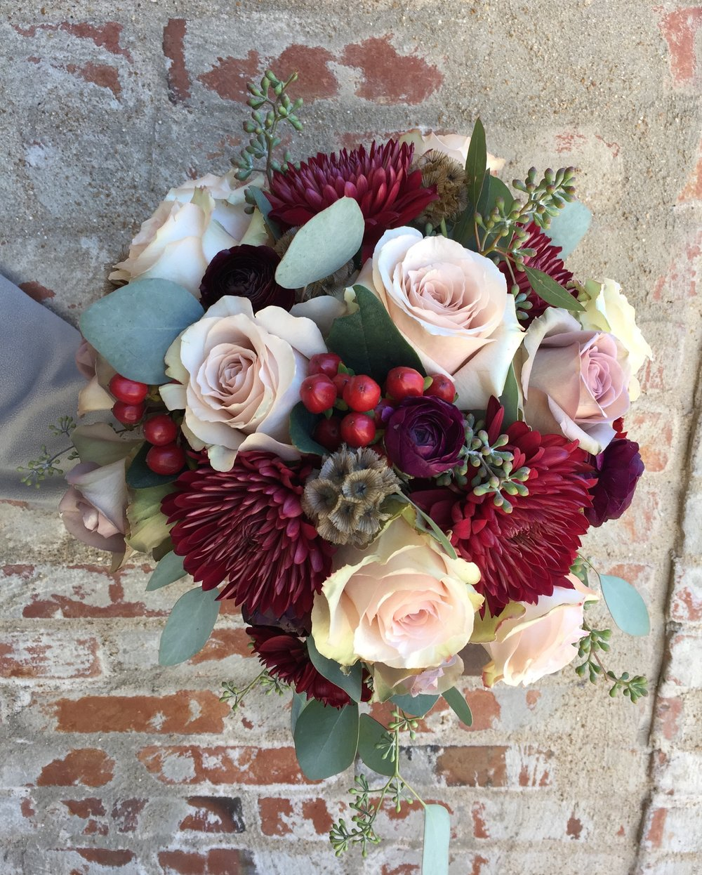 Roses, burgundy fujis, scabiosa pods, and hypericum.